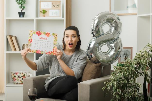 Überraschtes schönes mädchen am glücklichen frauentag, der den kalender hält, der auf einem sessel im wohnzimmer sitzt
