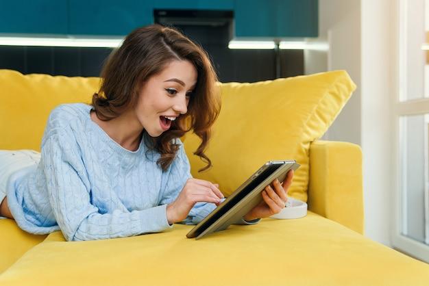 Überraschtes schönes mädchen benutzt tablet, während es sich auf einer bequemen, stilvollen couch in einem gemütlichen zuhause ausruht.