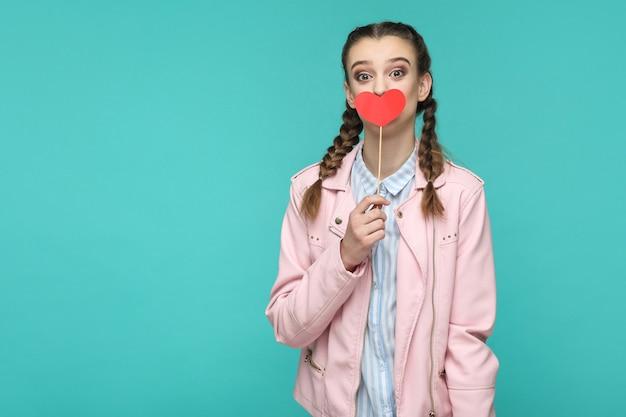 Überraschtes schönes mädchen im lässigen stil, zopffrisur und rosa jacke, das rote herzaufkleber steht und hält und mit großen augen in die kamera schaut, indoor, einzeln auf blauem oder grünem hintergrund