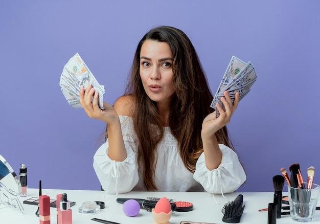 Überraschtes schönes mädchen sitzt am tisch mit make-up-werkzeugen, die geld in zwei händen lokalisiert auf lila wand halten