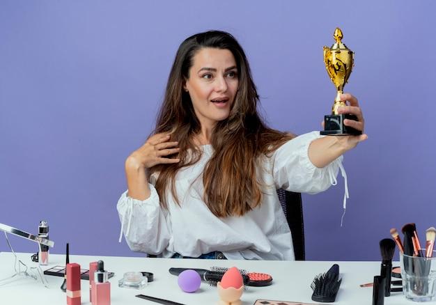 Überraschtes schönes mädchen sitzt am tisch mit make-up-werkzeugen hält und betrachtet gewinnerpokal isoliert auf lila wand