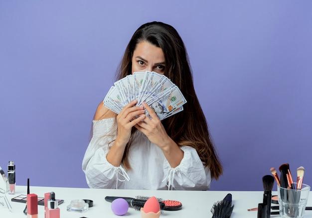 Überraschtes schönes mädchen sitzt am tisch mit make-up-werkzeugen hält und schaut über geld isoliert auf lila wand