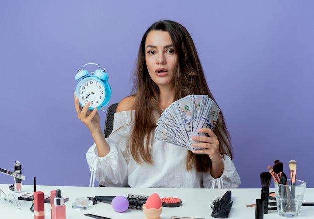 Überraschtes schönes mädchen sitzt am tisch mit make-up-werkzeugen hält wecker und geld isoliert auf lila wand