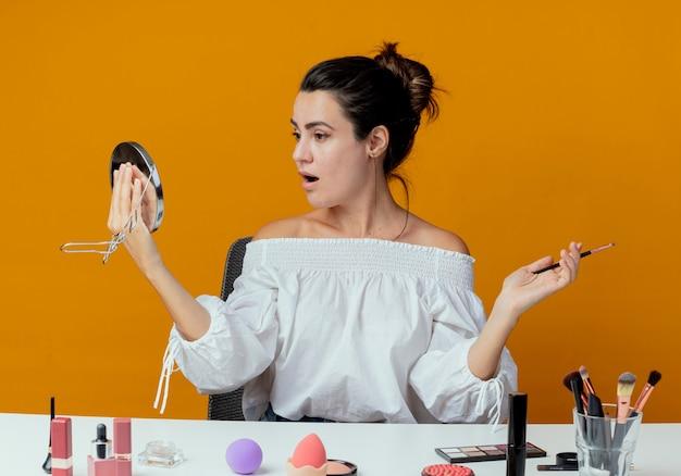 Überraschtes schönes mädchen sitzt am tisch mit make-up-werkzeugen schaut auf spiegel und hält make-up-pinsel isoliert auf orange wand