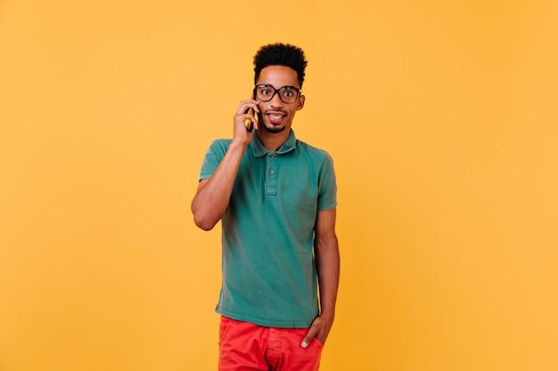 Überraschtes schwarzes männliches modell, das am telefon spricht. stilvoller afrikanischer kerl in den gläsern, die mit smartphone aufwerfen.