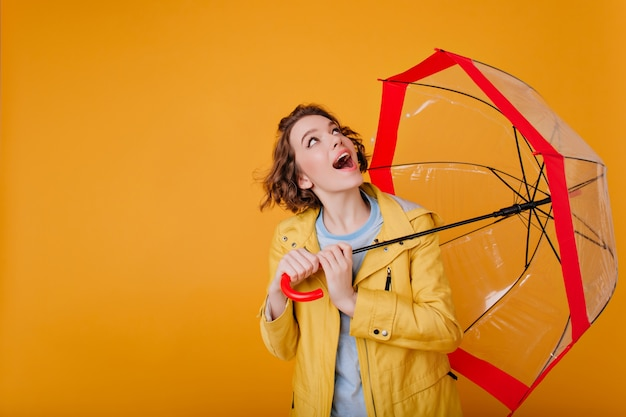 Überraschtes sorgloses mädchen im trendigen mantel, der nach oben schaut und regenschirm hält. studioaufnahme der hübschen frau mit dem gewellten haar, das mit sonnenschirm auf gelber wand aufwirft.