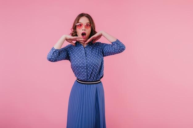 Überraschtes süßes mädchen in der weinlesekleidung, die auf rosa wand aufwirft. faszinierende lockige dame in blauer bluse, die erstaunen ausdrückt.