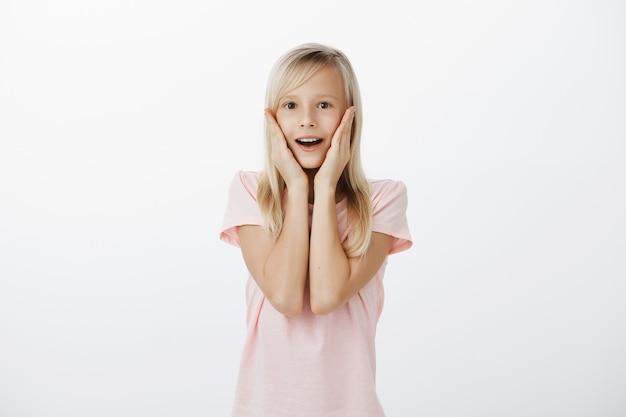 Überraschtes und beeindrucktes blondes mädchen, das glücklich aussieht