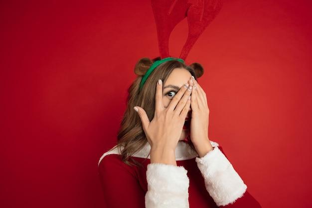 Überraschtes verstecktes gesicht. konzept von weihnachten, neujahr, winterstimmung, feiertagen. . schöne kaukasische frau mit langen haaren wie santa's rentier anziehende geschenkbox.
