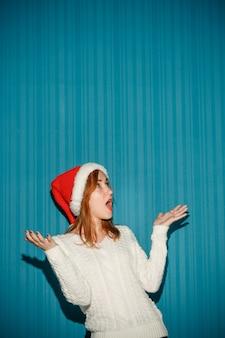 Überraschtes weihnachtsmädchen, das eine weihnachtsmütze auf dem blauen studiohintergrund trägt
