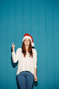 Überraschtes weihnachtsmädchen, das eine weihnachtsmütze trägt, die auf dem blauen studiohintergrund zeigt