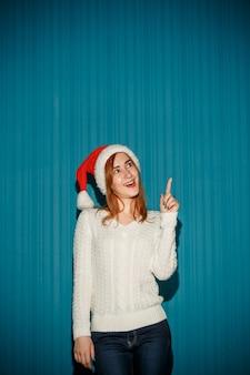Überraschtes weihnachtsmädchen, das eine weihnachtsmütze trägt, die oben auf dem blauen studiohintergrund zeigt, der oben zeigt