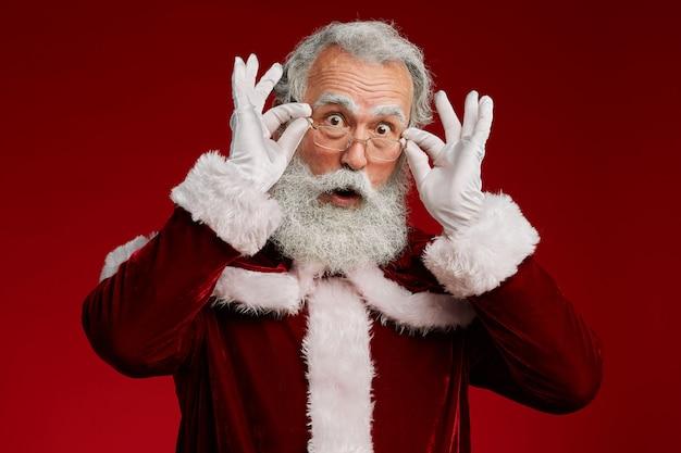 Überraschtes weihnachtsmann, das über brillen schaut
