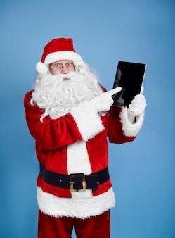 Überraschtes weihnachtsmann, der digitalanzeige hält