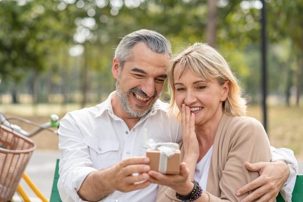 Überraschung des älteren mannes des glücklichen paars, die seiner frau geschenkbox beim entspannen und sitzen auf der bank im park gibt