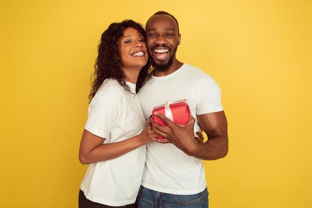 Überraschung geben. valentinstagfeier, glückliches afroamerikanerpaar lokalisiert auf gelbem studiohintergrund. konzept der menschlichen gefühle, gesichtsausdruck, liebe, beziehungen, romantische feiertage.