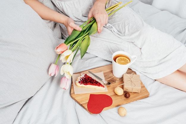 Überraschung im bett. frühstück, blumen und ein geschenk für ein mädchen zum valentinstag. herzlichen glückwunsch zum 14. februar.