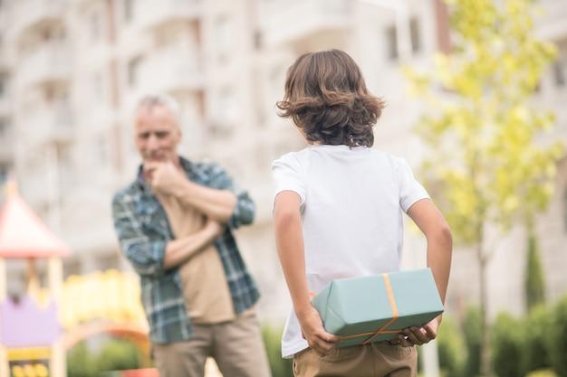 Überraschung. junge, der eine geschenkbox hält, während papa nachdenklich schaut