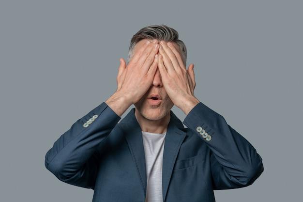 Überraschung. mann in dunkler businessjacke, die gesicht mit handflächen mit offenem mund auf grauem hintergrund bedeckt