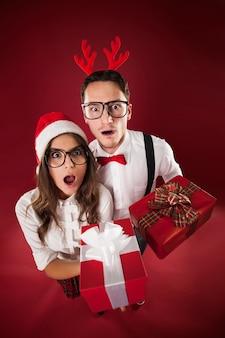 Überraschungs-nerd-paar, das weihnachtsgeschenke hält