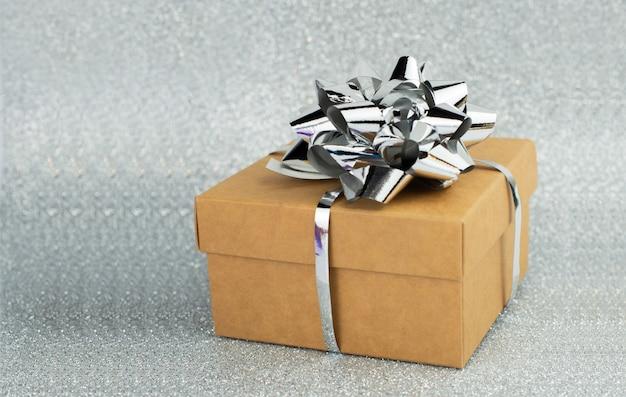 Überraschungsgeschenkbox auf silber mit bogenhintergrund mit bokeh-nahaufnahme