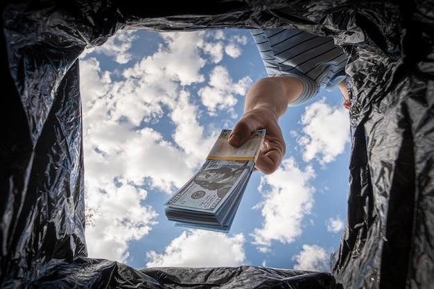 Überschüssiges bargeld loswerden, auf bargeldlose zahlung umstellen. das konzept der inflation. dollar in den mülleimer werfen