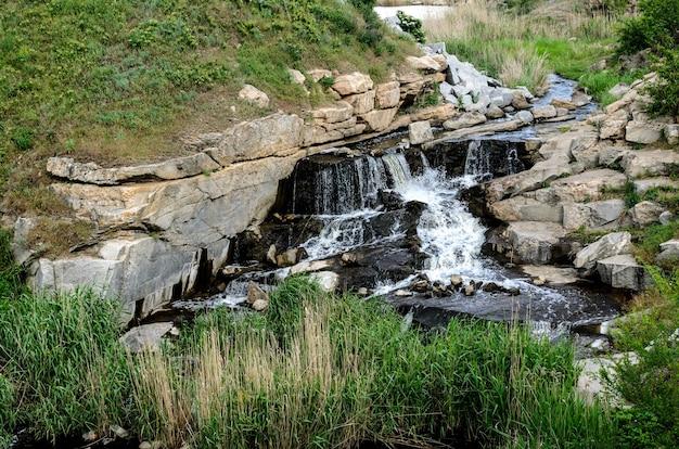 Überschwemmte industrielle granitkarriere mit wasserfällen