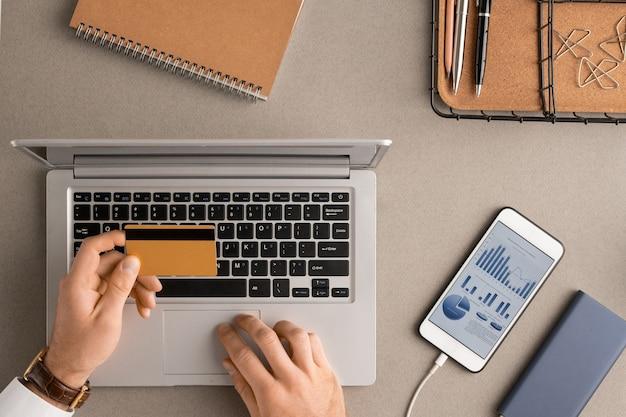 Übersicht der hände des jungen zeitgenössischen geschäftsmannes mit kreditkarte über laptop-tastatur, die für seine bestellung im online-shop bezahlen wird
