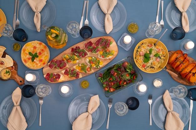 Übersicht der servierten festlichen tafel mit hausgemachtem vegetarischem salat, kuchen, sandwiches, pasta, gebackenen kürbisscheiben, limonade und anderen sachen
