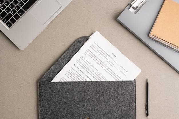 Übersicht über den finanzvertrag in einem großen grauen umschlag, umgeben von laptop, ordner mit zwischenablage mit dokumenten und heft am arbeitsplatz