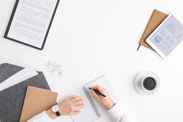 Übersicht über die hände eines jungen maklers oder wirtschaftswissenschaftlers mit einem stift über einer leeren seite des notizbuchs, die den arbeitsplan für den neuen tag aufschreiben wird