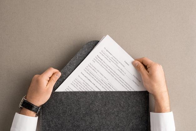 Übersicht über die hände eines zeitgenössischen managers oder maklers, der vor dem lesen und unterzeichnen einen finanzvertrag aus einem großen grauen umschlag nimmt