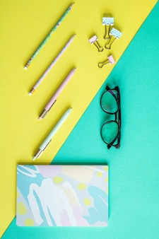 Übersicht über stifte und clips auf gelbem hintergrund und notizbuch mit brille auf blauem hintergrund