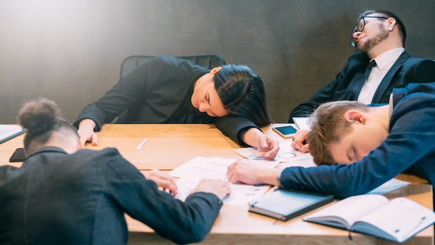 Überstunden und fristen. erschöpftes professionelles team. junge geschäftsleute, die im konferenzraum ein nickerchen machen.