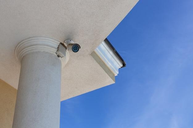 Überwachungs-cctv-kamera (closed circuit television) auf dem dach des privathauses auf blauem himmel hintergrund installiert