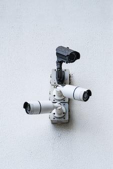 Überwachungskameras auf weißem modernem gebäude, technologiekonzept