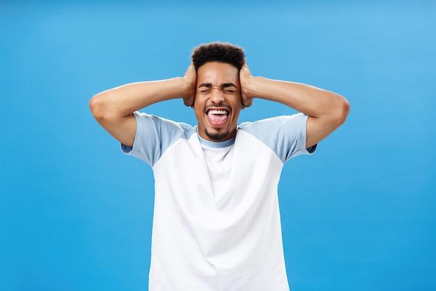 Überwältigend von vielen informationen. porträt eines beunruhigten afroamerikanischen männlichen studenten im t-shirt, der die hände auf dem kopf hält und mit geschlossenen augen schreit, die die beherrschung über die blaue wand verlieren