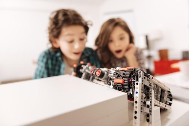 Überwältigende emotionen in uns. schockiert überraschte emotionale kinder, die im naturwissenschaftlichen klassenzimmer sitzen und den roboter betrachten, während sie technikunterricht haben