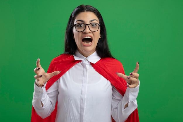 Überwältigtes junges kaukasisches superheldenmädchen, das eine brille trägt, die ihren mund in schockzustand offen hält, hält hände in der luft, die kamera lokalisiert auf grünem hintergrund mit kopienraum betrachtet