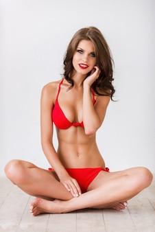 Überzeugt von ihrer schönheit. schöne junge frau mit braunen haaren im roten bikini, die auf dem holzboden sitzt