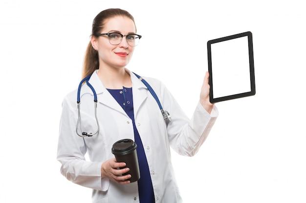 Überzeugte ärztin des attraktiven kaukasischen brunette, die im büro mit dem tasse kaffee zeigt tablette in ihren händen steht