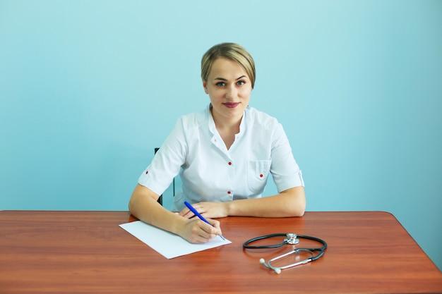 Überzeugte ärztin mit einem stethoskop sitzt am tisch und schreibt empfehlungen aus