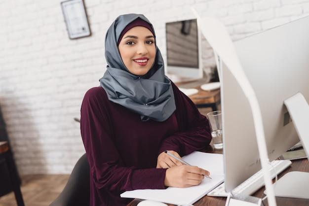 Überzeugte arabische geschäftsfrau, die am computer arbeitet.