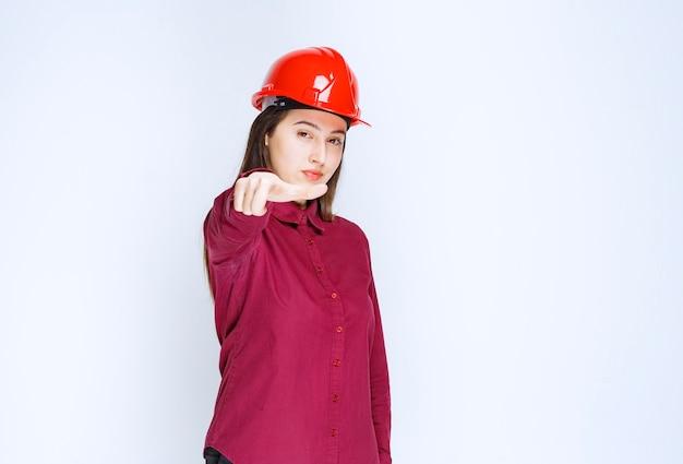 Überzeugte architektin im roten harten helm, die über weißer wand steht und posiert.