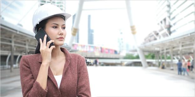Überzeugte asiatische berufstätige frau trägt sturzhelm und benutzt mobiltelefon bei draußen stehen.