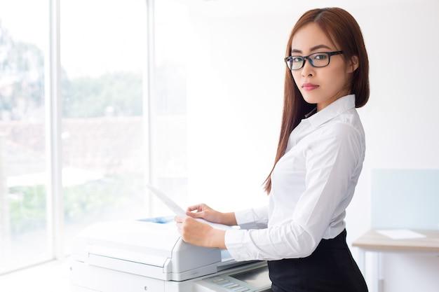 Überzeugte asiatische frau, die fotokopierer in office