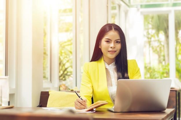 Überzeugte asiatische geschäftsfrau beim arbeiten mit laptop