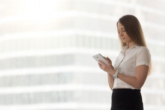 Überzeugte erfolgreiche geschäftsfrau, die unter verwendung der digitalen tablettenanwendungen, kopienraum hält