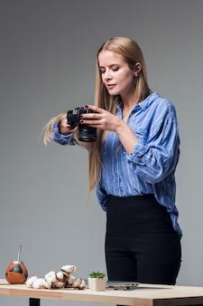 Überzeugte frau im blauen hemd, das lebensmittelfotos macht