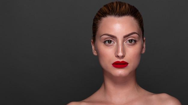 Überzeugte frau mit rotem lippenstift an
